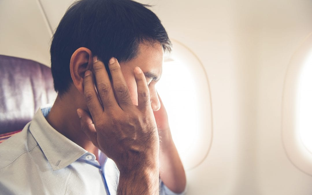 man on plane with fingers in ears | Hear More Associates