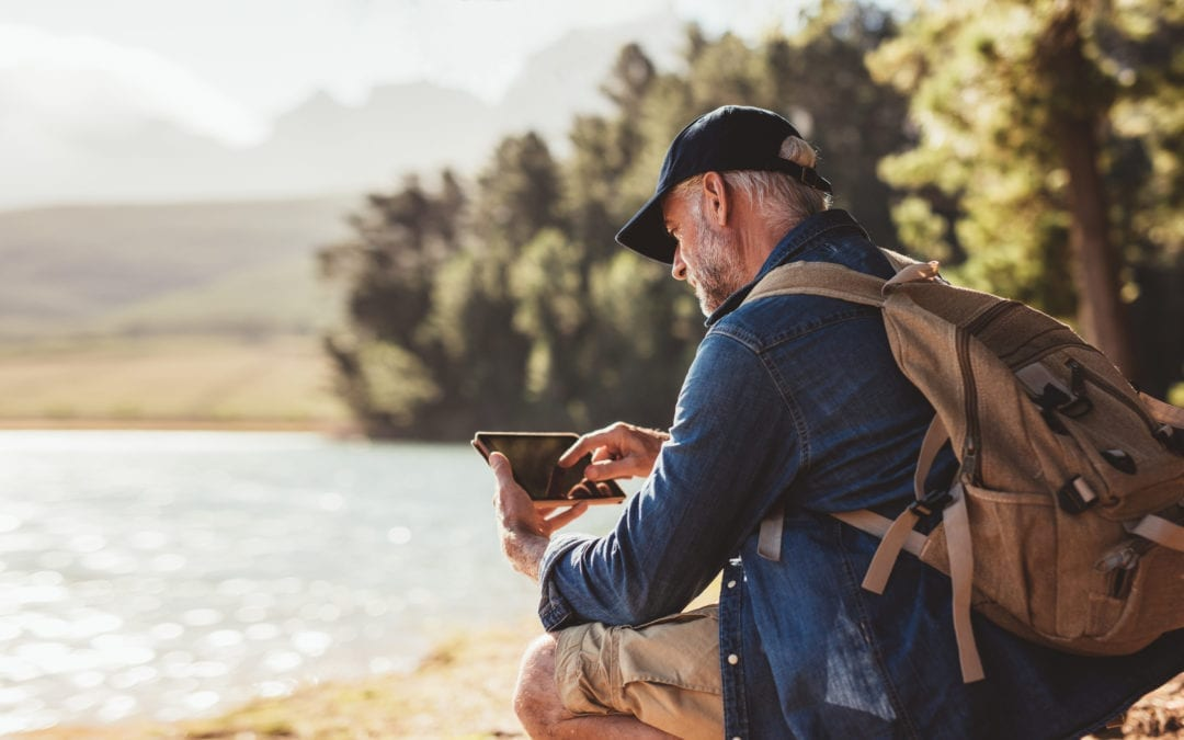 man on tablet at lake | Hear More Associates