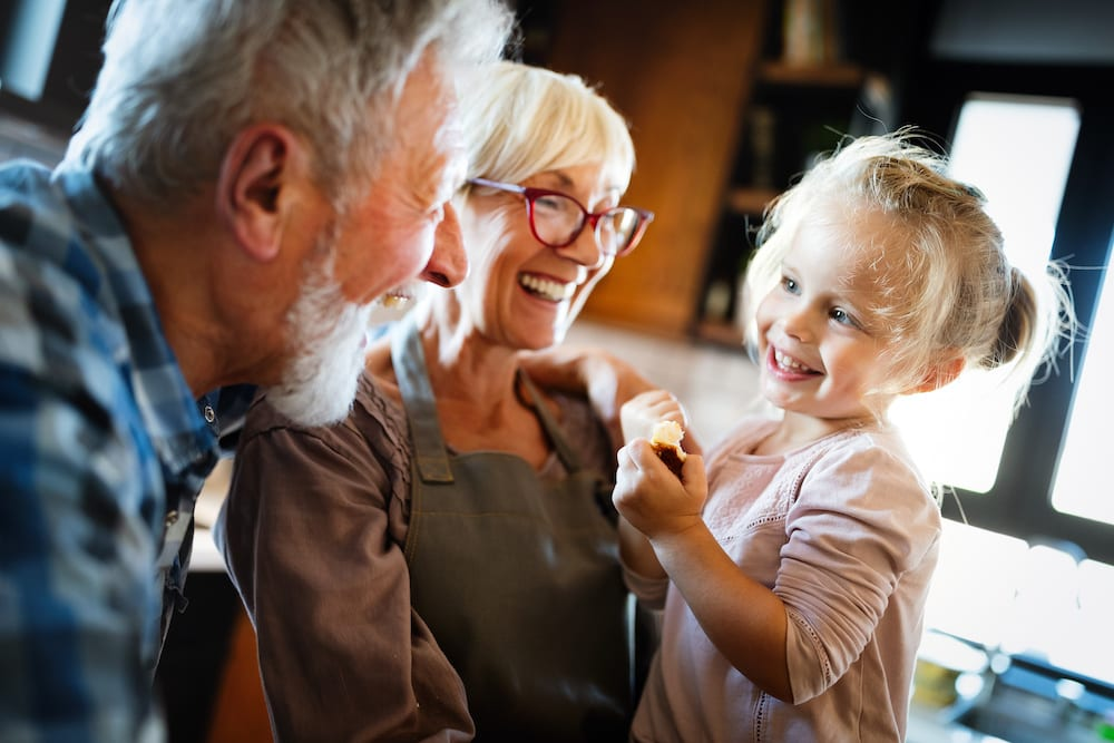 Happy grandparents having fun times with children at home | Hear More Associates