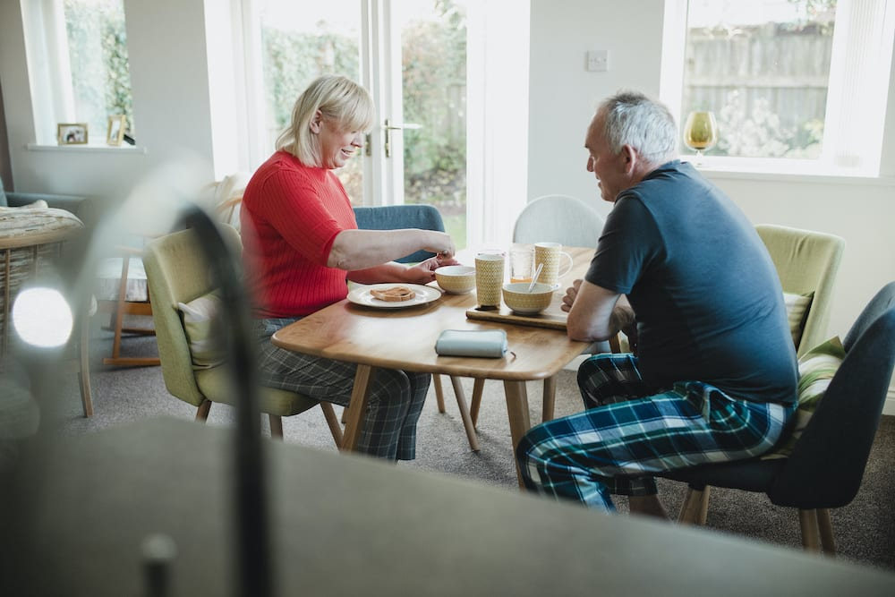 Mature Couple Enjoying Breakfast at Home | Hear More Associates
